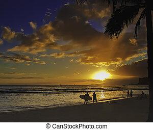 Sunset on Waikiki Beach with surfers walking along beach,...