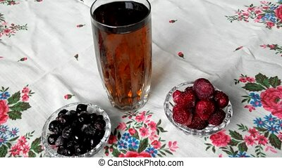 Crystal glass with a fruit drink. Berries near glass of...