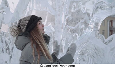 young woman smiling at the ice sculptures, winter gloves....