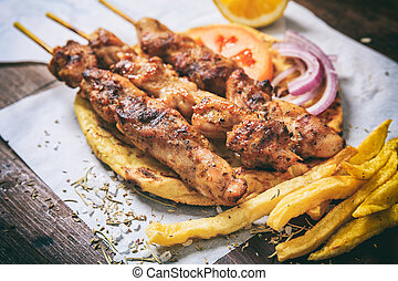 Meat skewers on a wooden background