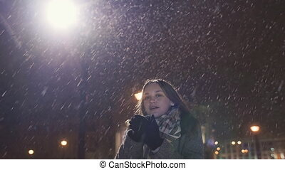 A young girl on the background of evening city warms up cold hands. In light of the city lights snowing.