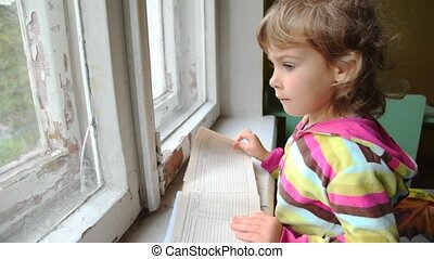 girl turns over the pages of medical report - little girl...