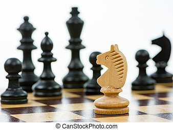 White knight against a superiority of black chess pieces on...