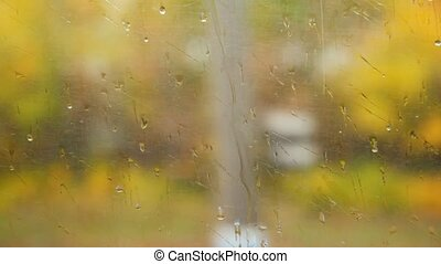water drops on window of moving transport, autumn background
