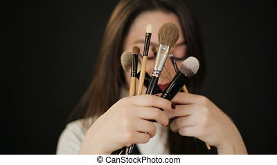 Woman hiding behind makeup brushes - Beautiful woman...