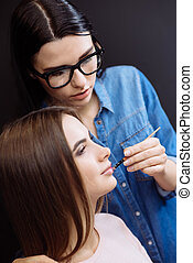 Serious concentrated makeup artist using a lip brush