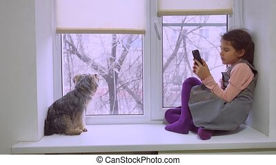 girl teen playing web online game for smartphone and dog...
