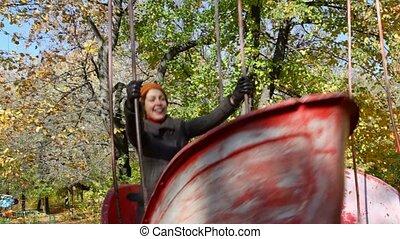 woman teetering on swing boat in park