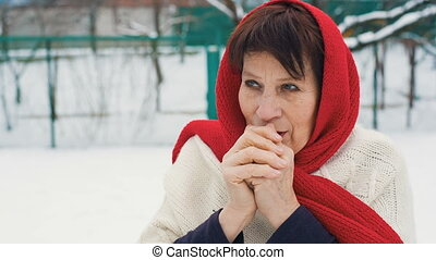 Elderly Woman Warms Hands - Elderly woman in red scarf warms...