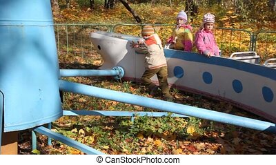 boy pushes on carrousel with girls on playground - boy...