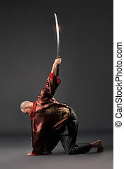 Men exercising with sword in studio - Men in chinese...