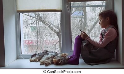 girl teen playing online the game for smartphone and pet dog...