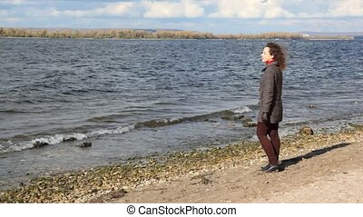 woman stands on bank and looks at river