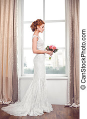 Wedding. Beautiful bride indoors with bouquet of flowers...