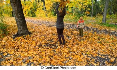 woman and boy throwing leaves in park