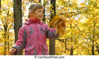 girl waving hand with leaves in park