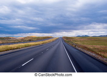 Long straight road going cloudly horizon in California -...