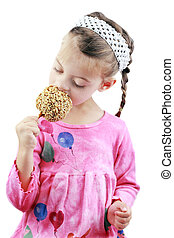 Child Eating a Caramel Apple - Adorable little girl eats a...