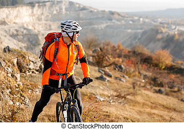 cyclist-traveler with a backpack on mountainbike -...