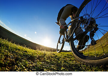 man cyclist stand with mountain bike at sunset - low angle...