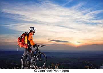 cyclist on mountain-bike background of beautiful sunset. -...