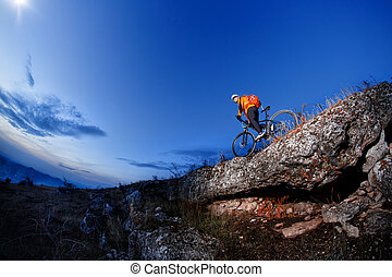 Cyclist Riding the Bike Down Hill on the Mountain Rocky at Sunset.