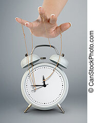 Hand puppeteer manipulating clock, time management concept