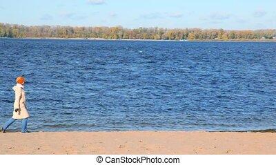 woman walking along sandy bank