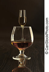 Glasses with white wine and cognac or whisky on mirror...