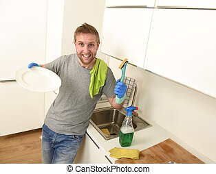 young happy unshaven man in rubber washing gloves doing the...