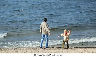 man and boy throws stones at river - man and boy in sandy...