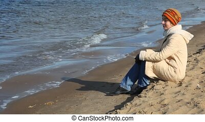 woman sits on sandy beach - one smiling woman dressed in...