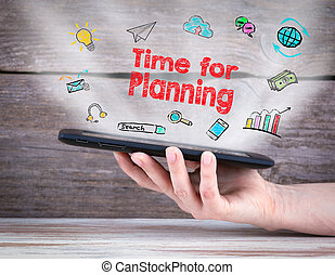 Time for planning. Tablet computer in the hand. Old wooden background