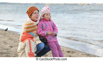 woman with kids sits on sandy bank
