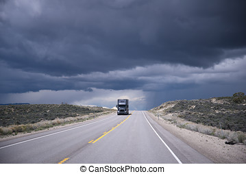 Dark grey semi-truck on highway and storming sky