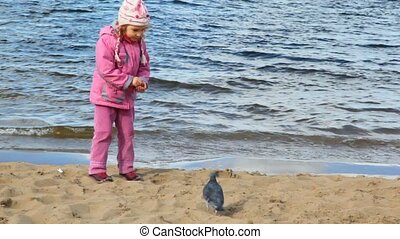 girl feeds pigeons on beach