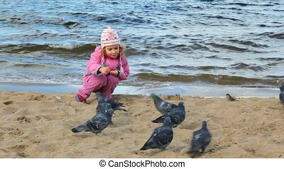 girl sits on beach and feeds pigeons