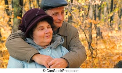 senior couple hugging against trees in park