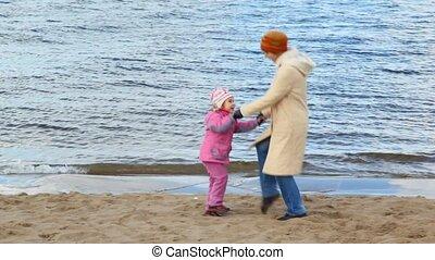 woman and girl dances on sandy beach