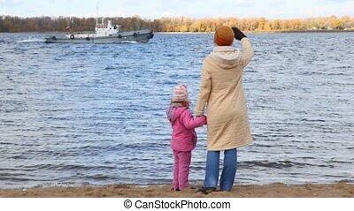 woman with girl on sandy bank