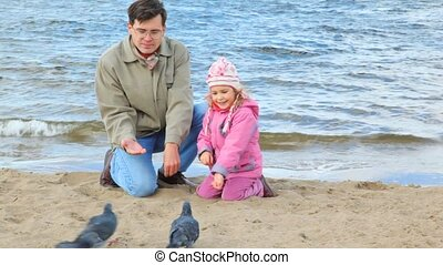 man and girl sits on beach and feeds pigeons