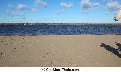 family runs on sandy beach - family of three having joined...