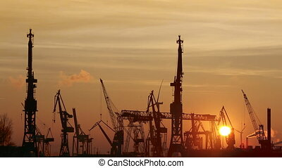 Silhouette of container harbor in Hamburg at sunset -...