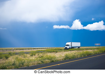 Semi truck trailer moving road with awesome landscape in California