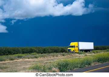 Yellow semi truck going thrue green bushes and trees