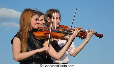 three musicians plays violin outdoors, sky in background