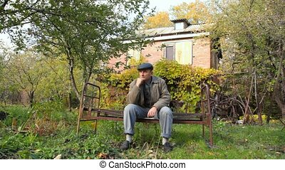 aged man sits on bench in garden - one aged man prop his...
