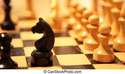 chessboard close up, knight goes back, piece forward