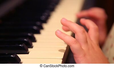 fingers of girl of pianos pressing key - side view of...