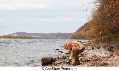 boy stand on river bank and throws stones in waves in autumn